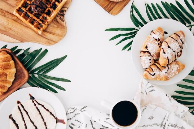 Croissant al forno; cialde; focacce; tortillas e caffè su sfondo bianco