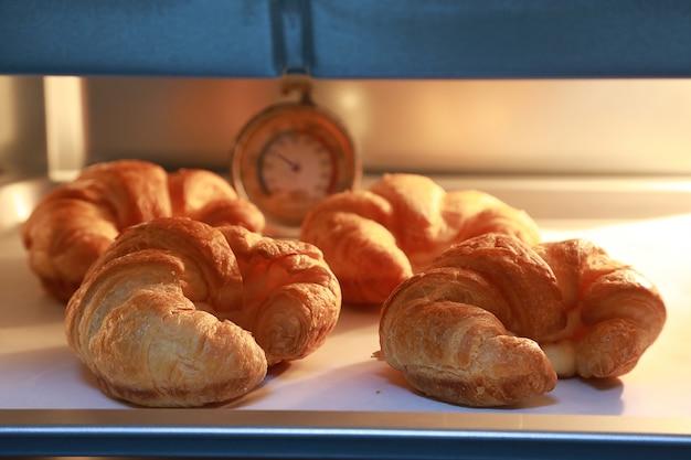 Croissant al forno con luci calde sullo sfondo del forno.