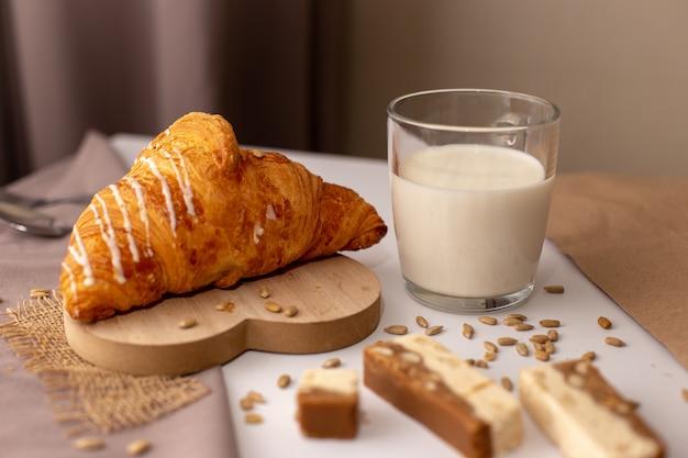 Croissant appetitoso, un bicchiere di latte e fette di sorbetto dolce. gustosa colazione