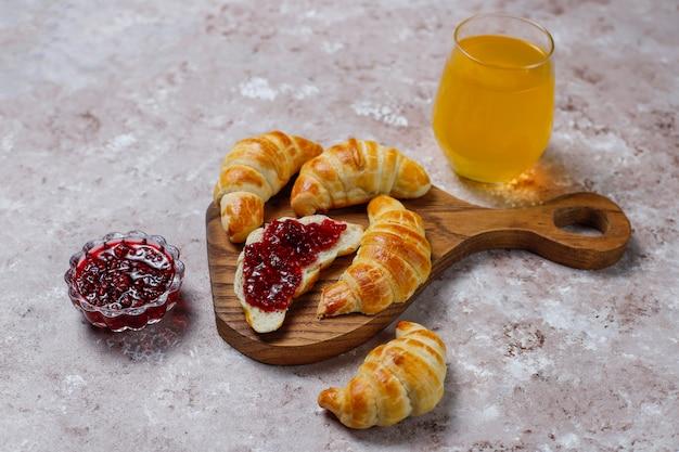 Croissant casalinghi saporiti freschi con l'inceppamento di lampone su bianco grigio. pasticceria francese