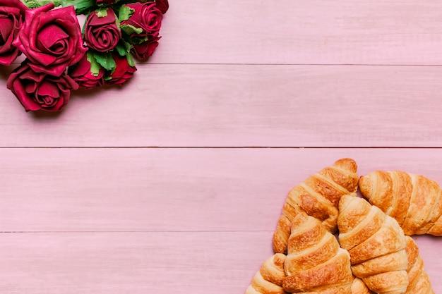 Croissant con bouquet di rose rosse sul tavolo