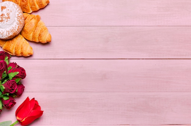 Croissant con bouquet di rose sul tavolo rosa