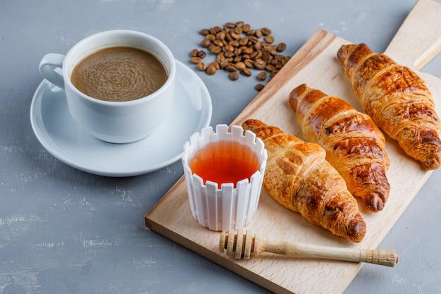 Croissant con caffè e fagioli, miele, mestolo vista dall'alto su intonaco e tagliere