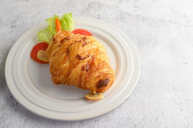 Croissant con hot dog sul piatto bianco