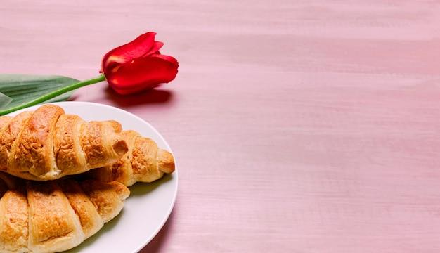 Croissant con tulipano rosso sul tavolo