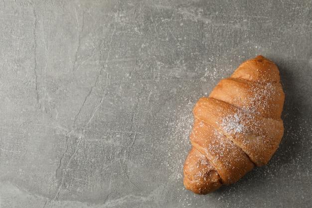 Croissant con zucchero a velo su sfondo grigio, vista dall'alto