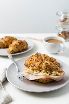Croissant del prosciutto e dell'uovo del primo piano su una zolla