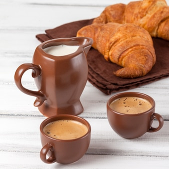Croissant di recente al forno sul tovagliolo marrone, crema, alle tazze di caffè in piatti ceramici su fondo di legno bianco. dolci freschi a colazione delizioso dessert fotografia del primo piano banner orizzontale