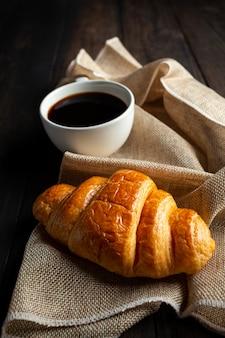 Croissant e caffè sul vecchio tavolo di legno.