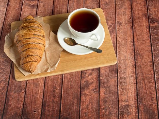 Croissant e tè della prima colazione su un tovagliolo del tessuto, superficie di legno scura