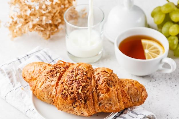 Croissant e tè per la colazione su sfondo bianco.