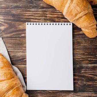 Croissant francesi di vista superiore e blocco note vuoto dello spazio della copia