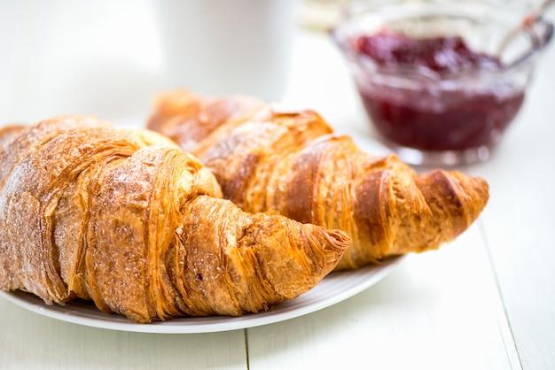 Croissant freschi con glassa, tazza di tè e marmellata di fragole