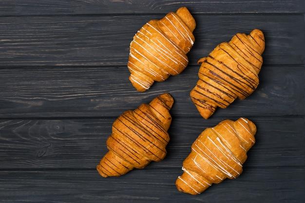 Croissant fresco su un fondo di legno nero. vista dall'alto copia spazio