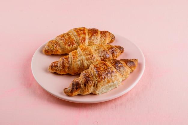 Croissant in una vista dell'angolo alto del piatto su una tavola rosa
