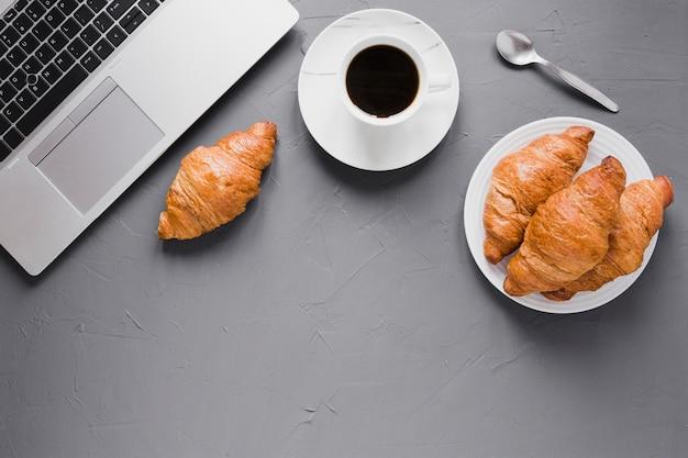 Croissant piatti laici caffè e laptop con spazio di copia