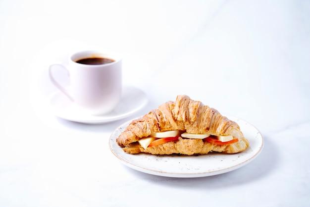 Croissant ripieni di formaggio e pomodoro e una tazza di caffè