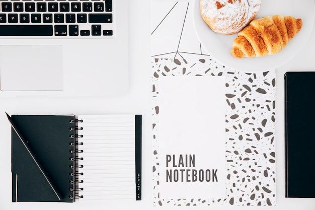 Croissant; semplice taccuino; il computer portatile; blocco note a spirale e matita sulla scrivania bianca