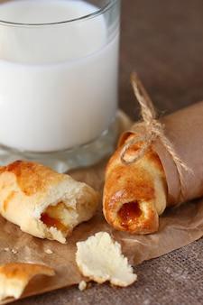 Croissant spezzati e briciole con marmellata di pesche avvolti in carta da regalo kraft e legati con stringhe con fiocchi e un bicchiere di latte su una tovaglia grigia ruvida.