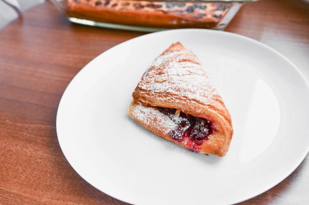 Croissant su un piatto bianco. cornetto sul piatto bianco, vista dall'alto. sweat dessert al forno in un dis.