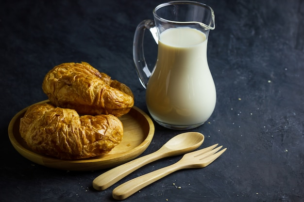Croissant sul piatto e sulla brocca di latte di legno sulla tavola