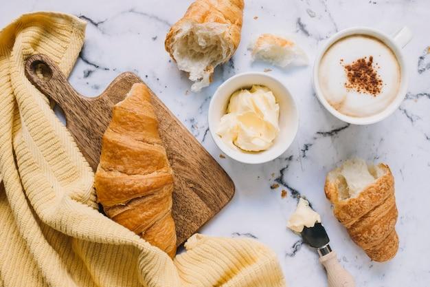 Croissant; tazza di burro e caffè sul piano in marmo con tovagliolo giallo