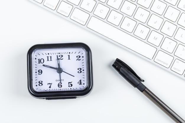 Cronometri il concetto con la penna, tastiera sulla disposizione piana del fondo bianco. immagine orizzontale