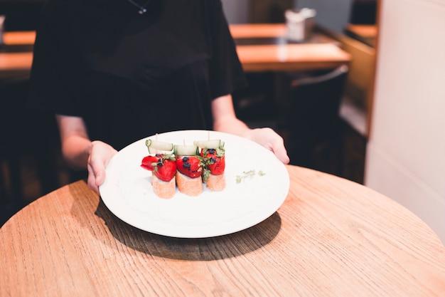 Crop cameriera tenendo piatto con panini aperti