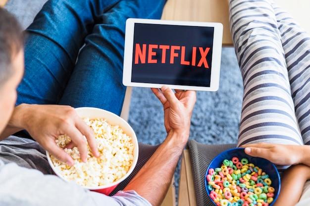 Crop coppia con snack guardando serie sul tablet