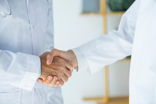 Crop i medici che si stringono la mano