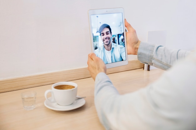Crop man holding tablet con selfie
