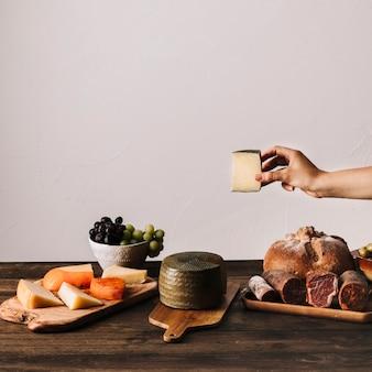 Crop mano che tiene il formaggio sul tavolo con il cibo