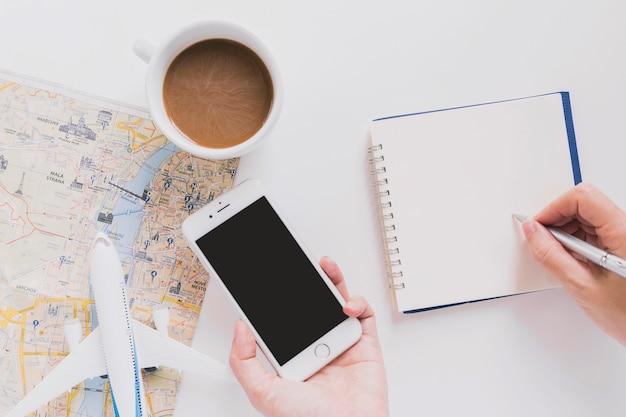 Crop persona con viaggio di pianificazione dello smarthone