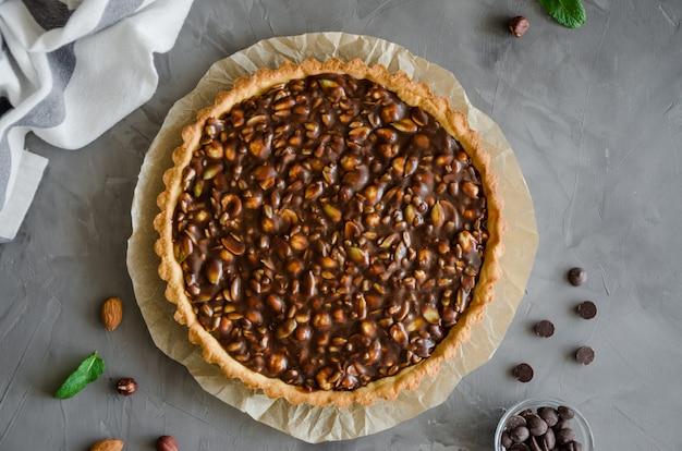 Crostata con caramello al cioccolato, nocciole, arachidi, mandorle e mix di semi su uno sfondo di cemento scuro. orientamento orizzontale.