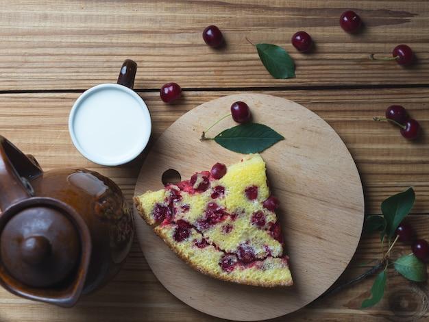 Crostata di ciliege casalinga sulla tavola di legno con latte