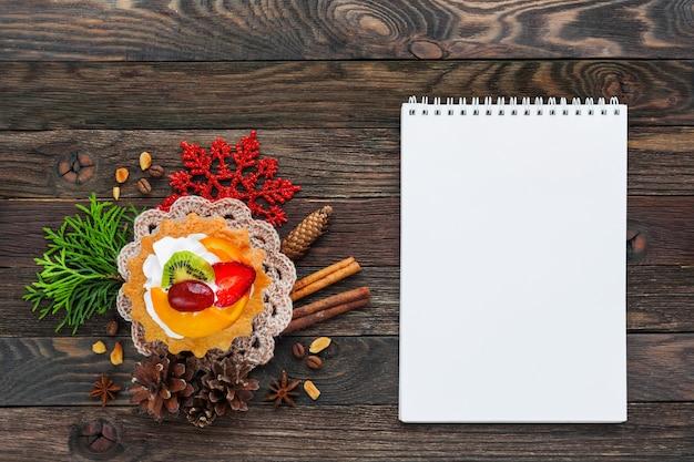 Crostata di frutta natalizia e decorazioni fiocco di neve, tovagliolo all'uncinetto, pigne. copyspace.