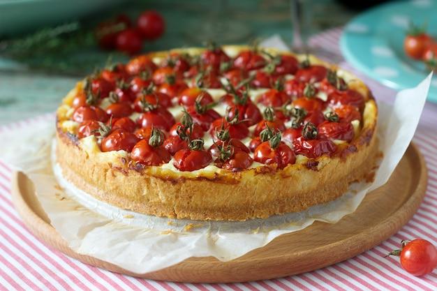 Crostata, torta o cheesecake con ricotta e pomodori, servito con vino rosso su un fondo di legno.