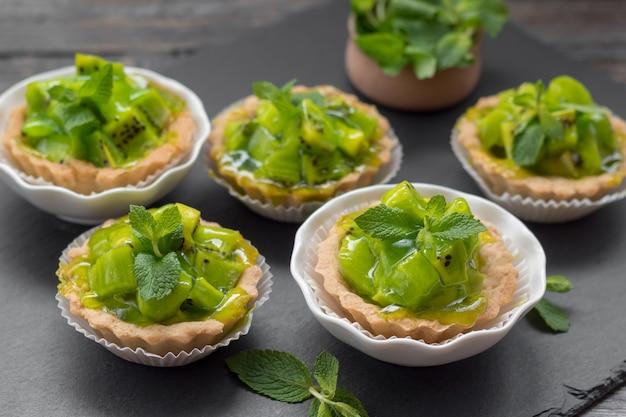 Crostate saporite del kiwi sul piatto dell'ardesia. dessert delizioso