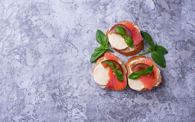 Crostini con salmone, mozzarella, pomodoro e basilico. antipasto o antipasto italiano