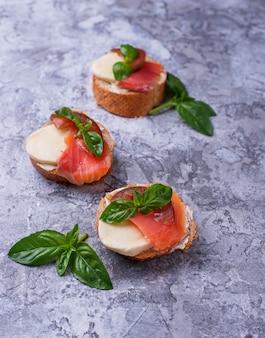 Crostini con salmone, mozzarella, pomodoro e basilico