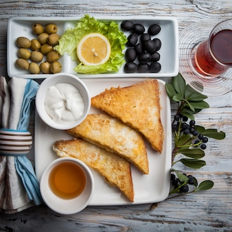 Crostini vista dall'alto con olive assortite e miele e bicchiere di tè bianco piatto