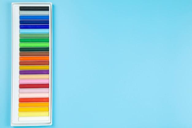Cryaon sul flatlay pastello del topview del copyspace di stile del fondo blu.