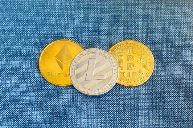 Crypto currency coin bitcoin, litecoin ed ethereum monete in portafoglio in pelle su sfondo blu.