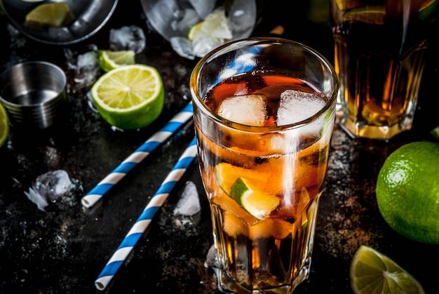 Cuba libre, long island o cocktail con tè freddo con alcol, cola, lime e ghiaccio, due bicchieri