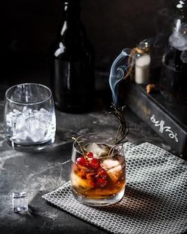 Cuba libre o long island ghiacciato cocktail con bevande forti, cola, lime e ghiaccio in bicchiere, bevanda fredda fredda o limonata. cocktail con il fuoco. cocktail con fumo.