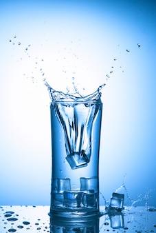 Cubetti di ghiaccio che cadono in un bicchiere d'acqua con spruzzata