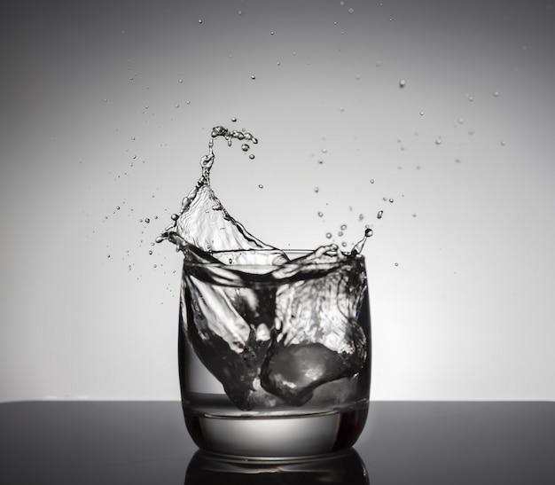 Cubetti di ghiaccio che spruzza in bicchiere d'acqua
