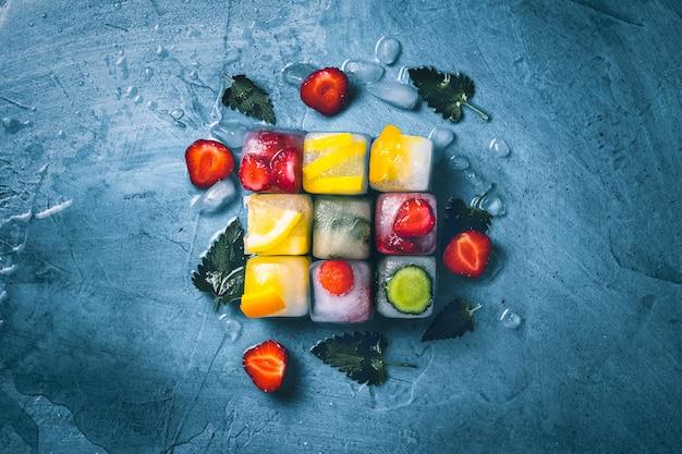 Cubetti di ghiaccio con frutta e ghiaccio rotto su una superficie di pietra blu con foglie di menta e frutta fresca. forma del cubo. menta, fragola, ciliegia, limone, arancia. vista piana, vista dall'alto