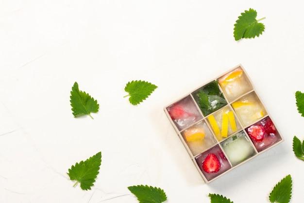 Cubetti di ghiaccio con frutta in stampo in silicone su una superficie di pietra bianca. concetto del gelato alla frutta, dissetante, estate. vista piana, vista dall'alto