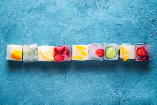 Cubetti di ghiaccio con frutta su una superficie di pietra blu. linea. menta, fragola, ciliegia, limone, arancia. vista piana, vista dall'alto